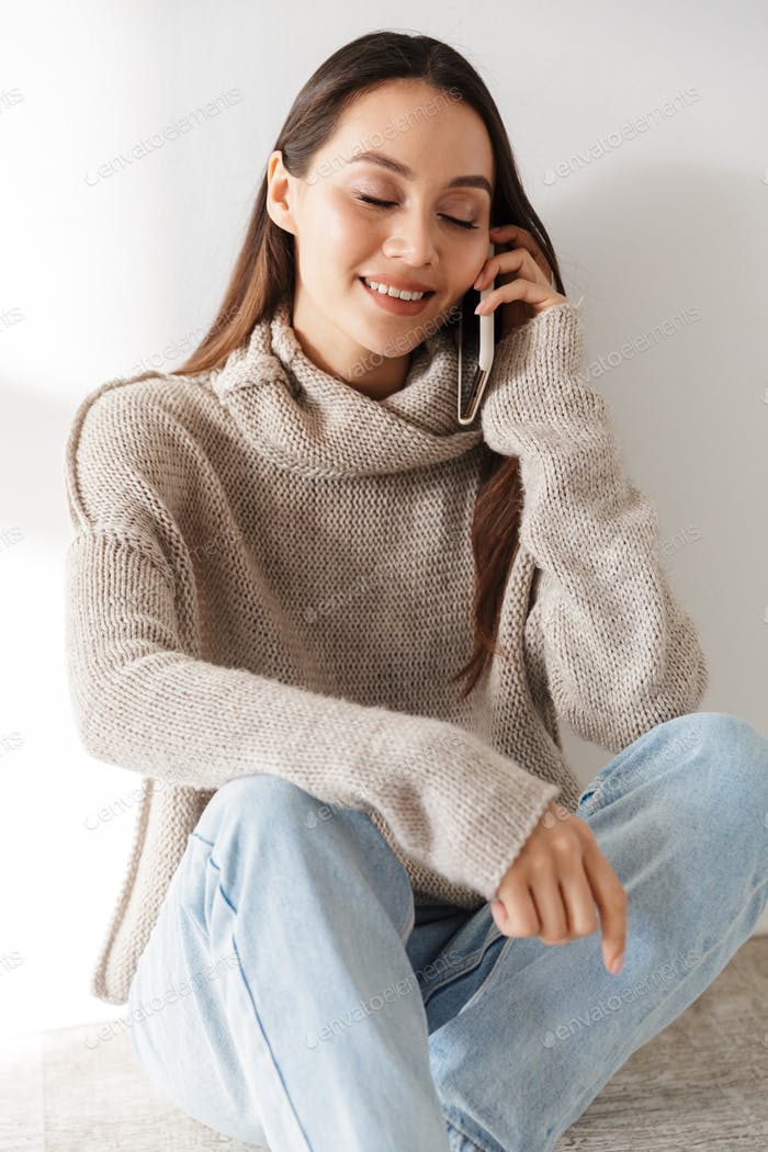 Image of smiling asian woman sitting and talking on smartphone