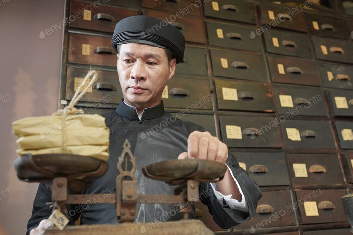 Traditional medicine practitioner checking weight of packages