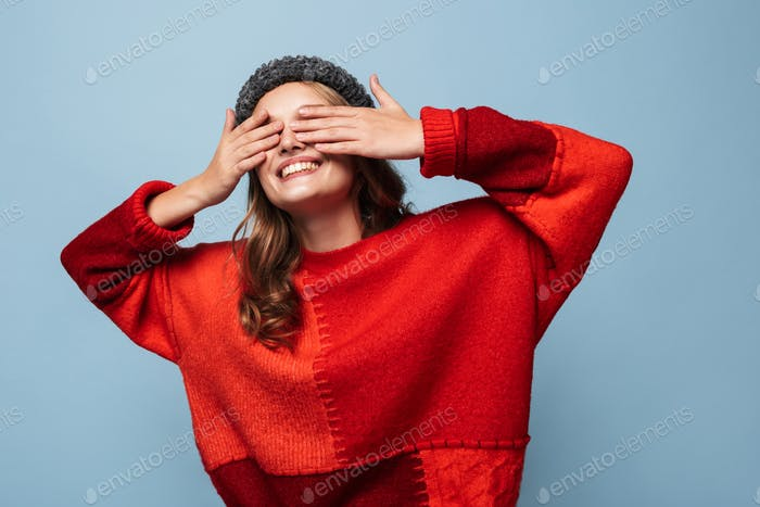 Beautiful smiling girl with wavy hair in hat and red sweater happily covering eyes with hands over