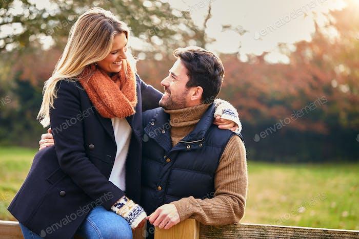 Liebendes Paar Auf Spaziergang Durch die Herbstlandschaft Sitzen Am Tor