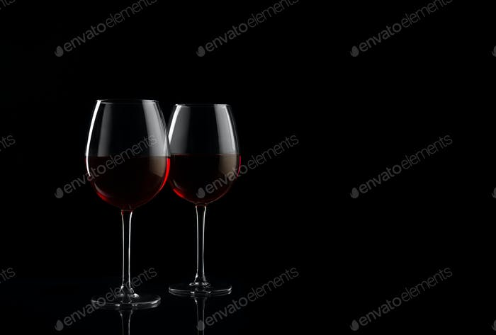 Two red wine glasses on a black background with copy space for your text
