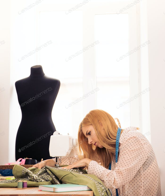 Designer using sewing machine in workshop