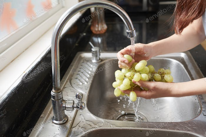 Woman rinsing organic grape