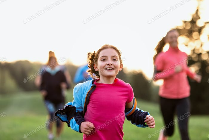 A portrait of small girl with large group of people running in nature