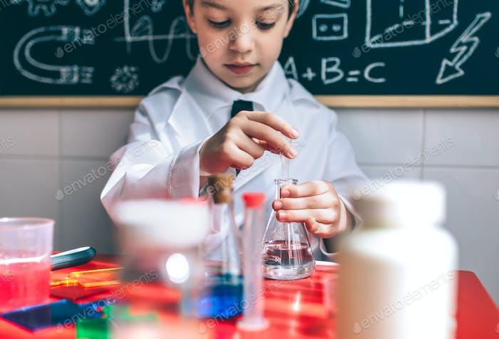 Niño serio jugando con líquidos químicos