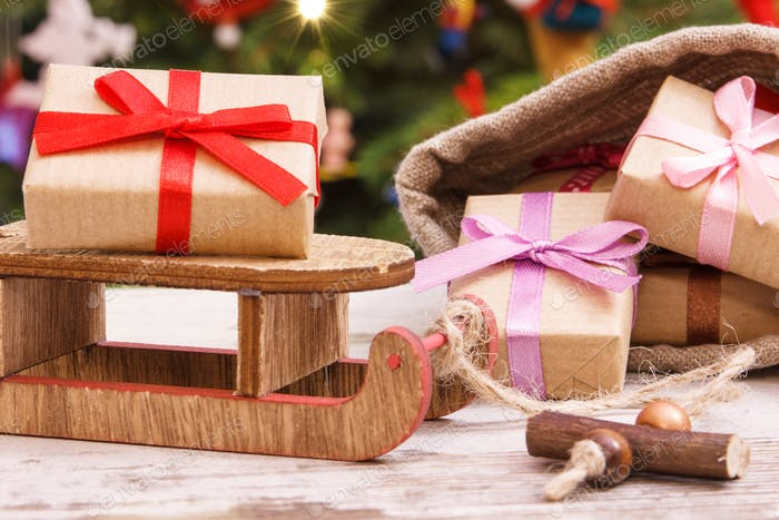 Gifts for Christmas on sled and in jute bag, festive tree with decoration, Christmas time concept