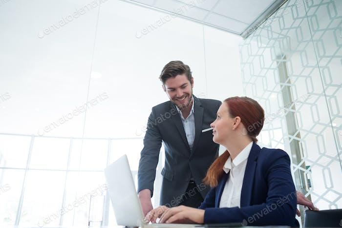 Business executives interacting while using laptop