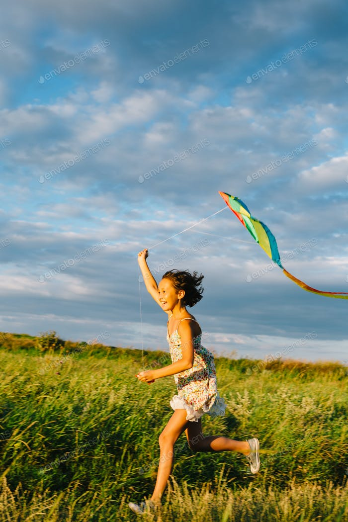 Cheerful girl running with kite