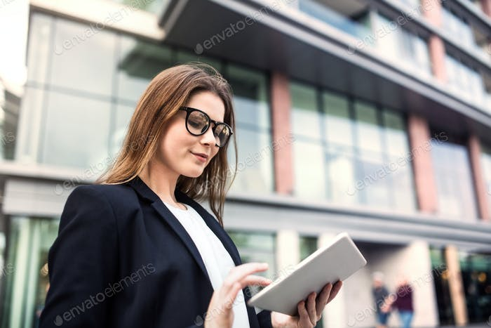 A young businesswoman using tablet outdoors in front of a building.