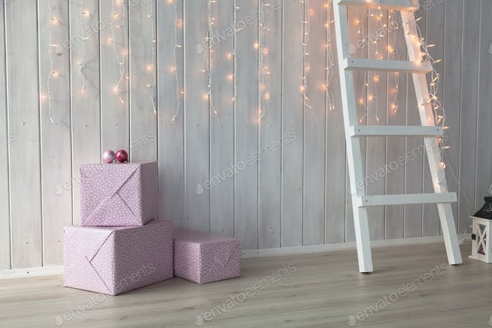 Christmas lights burning on a white wooden background with pink giftboxes and stairs