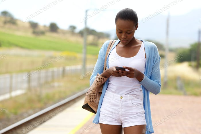 Young african woman with bag looking at mobile phone