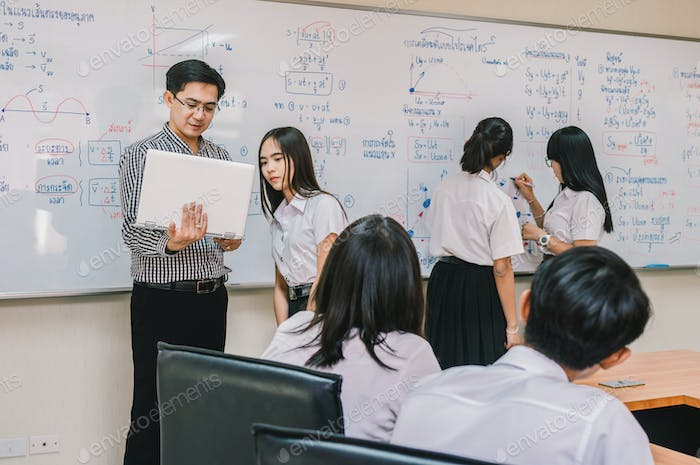 Asian teacher Giving Lesson to group of College Students in the classroom,