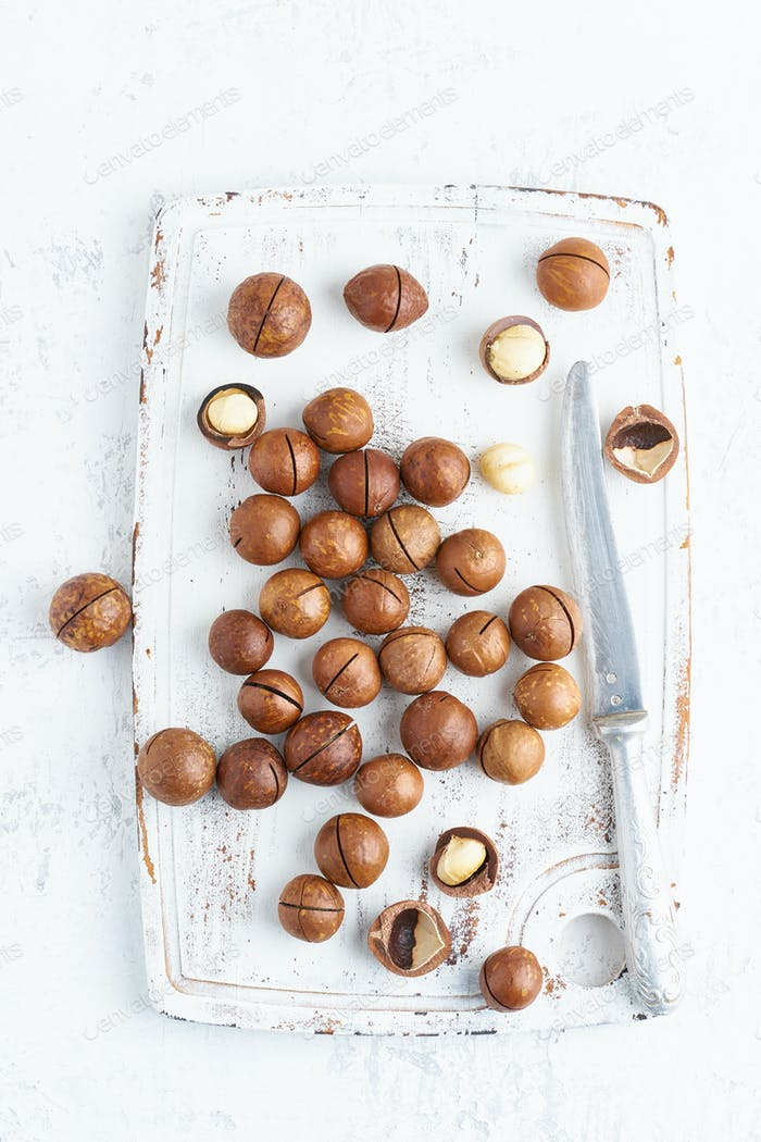 Plate with almonds in endocarp, whole and chopped open nuts in bulk on a cutting board