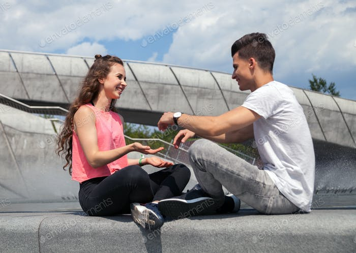 Young couple sitting outdoor and playing, happiness concept