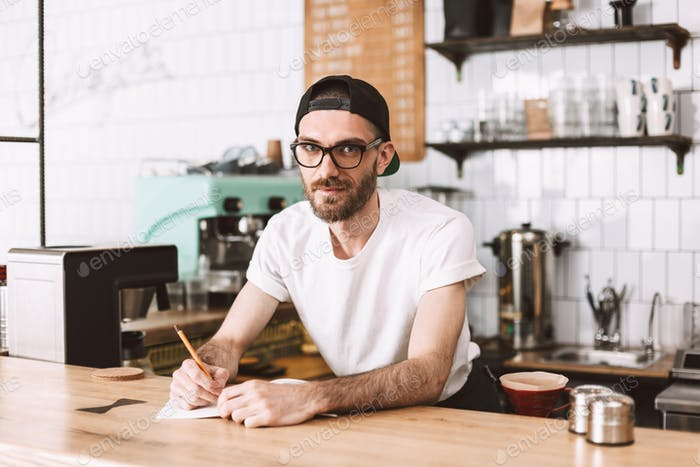 Smiling man in eyeglasses and cap standing behind bar counter with pencil and notepad