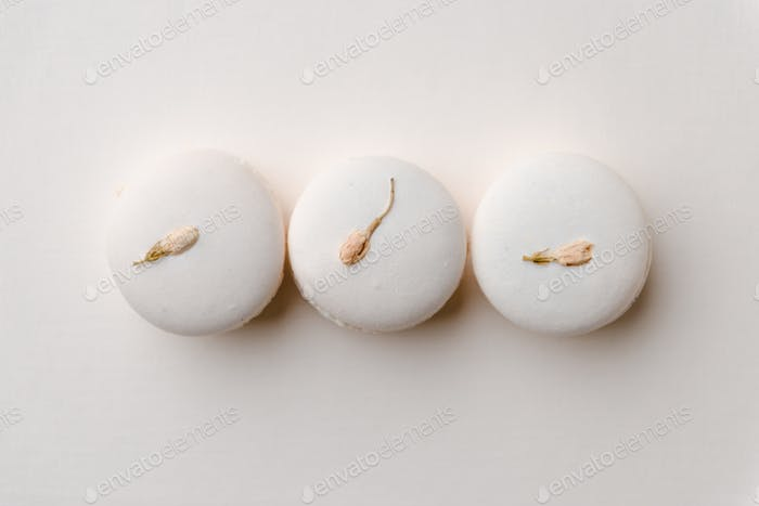 Sweet white macaroons on white table background.