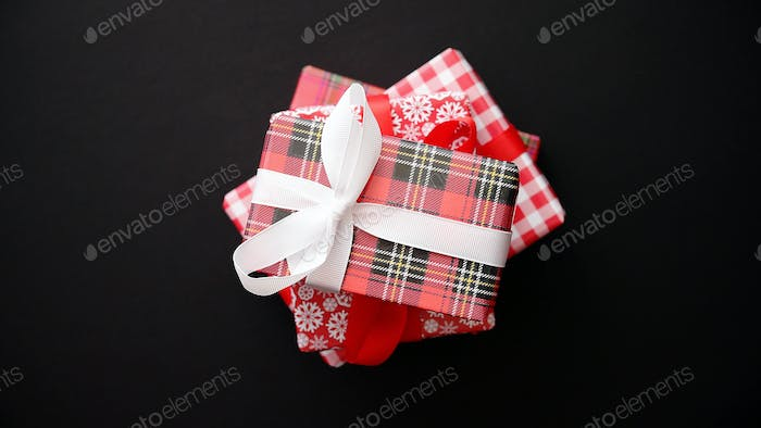 Red gift box with red bow on black table, top view