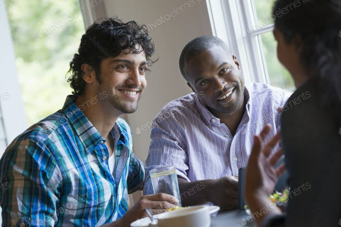 Tres personas sentadas en una mesa.