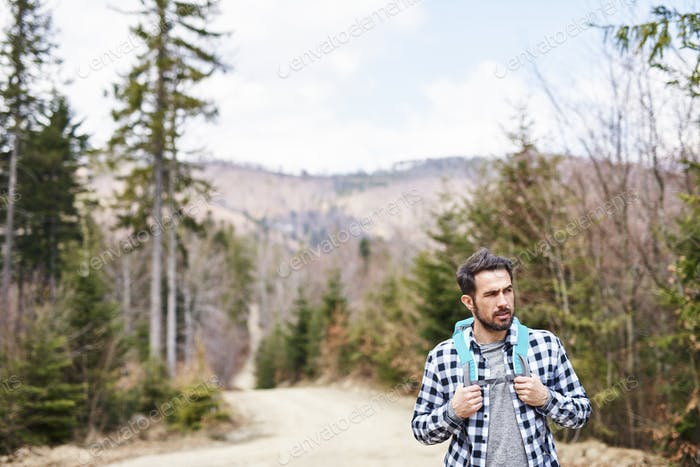 Front view of hiking man with backpack admiring at view