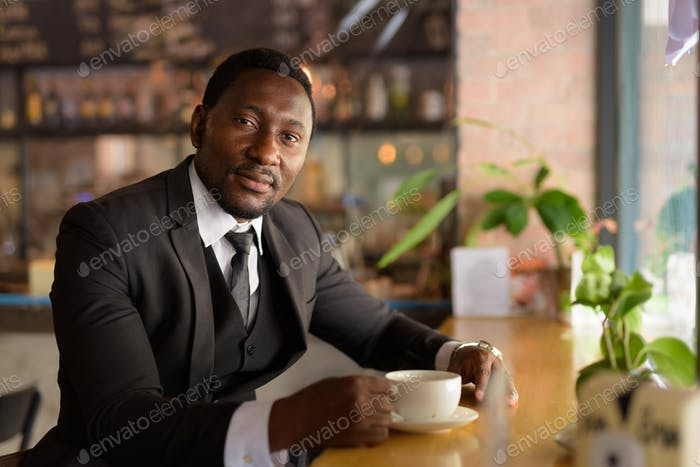 Handsome bearded African businessman relaxing inside the coffee shop
