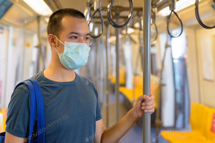Young Asian man with mask standing with distance inside the train