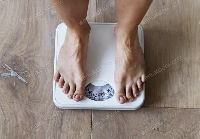 Pregnant woman weighing herself