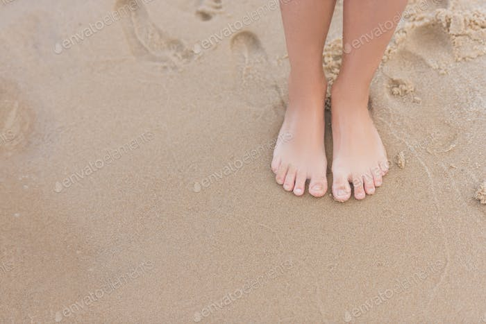 cropped view of child standing on sandy beach alone