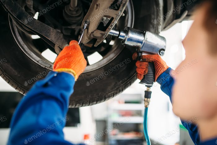 Technician with a wrench repair car suspension