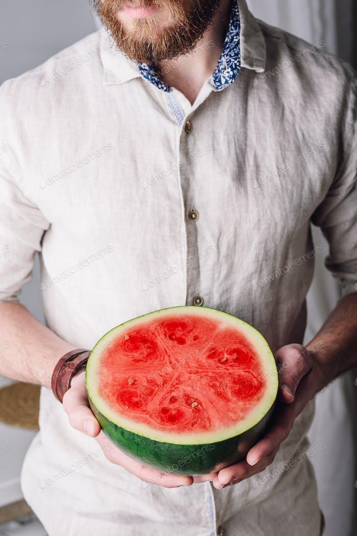 Bearded man with half of watermelon