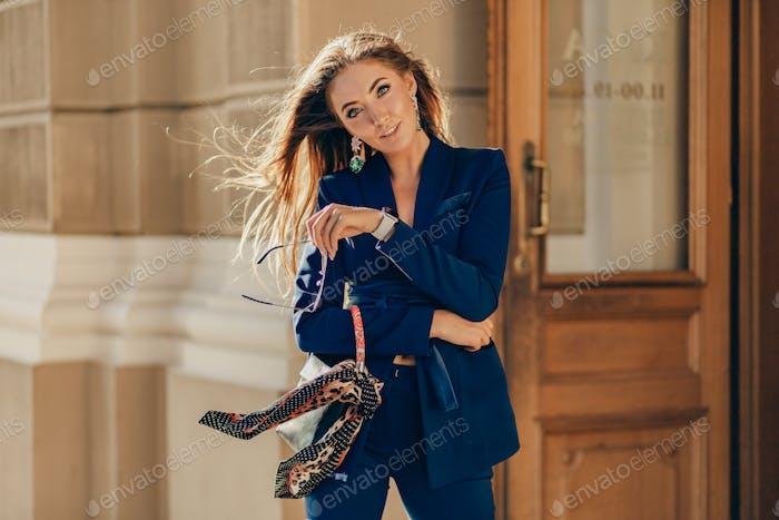 elegant attractive woman wearing blue stylish suit walking in street
