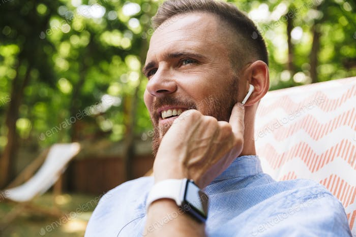 Happy young bearded man outdoors listening music