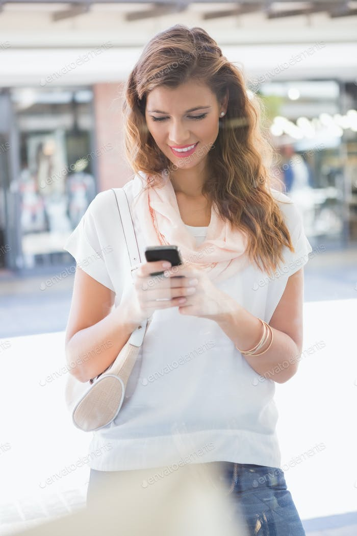 Smiling woman using smartphone at the shopping mall
