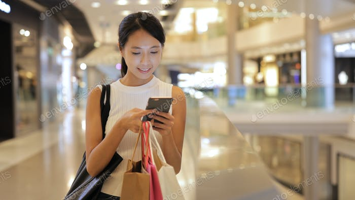 Woman looking at mobile phone and holding shopping bags in shopping center