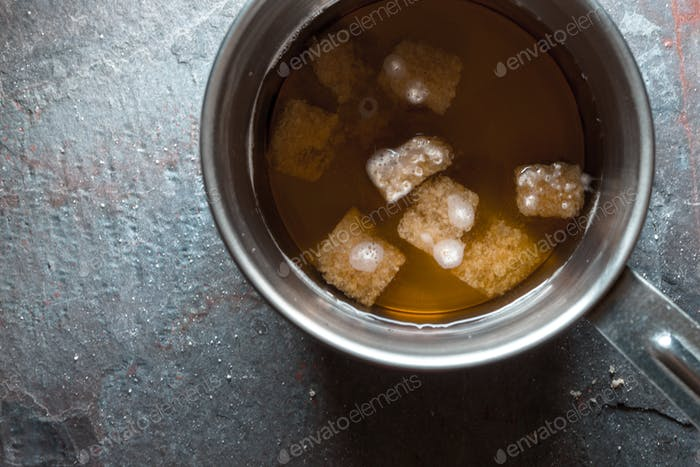 Preparation of syrup from cane sugar in a ladle