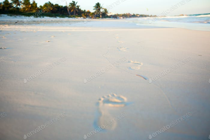 Human footprints on the white sandy beach
