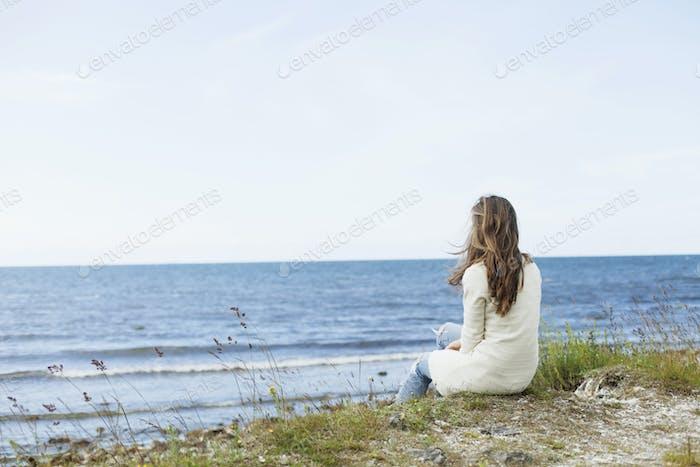 Vista trasera de la mujer sentada en la playa contra el cielo