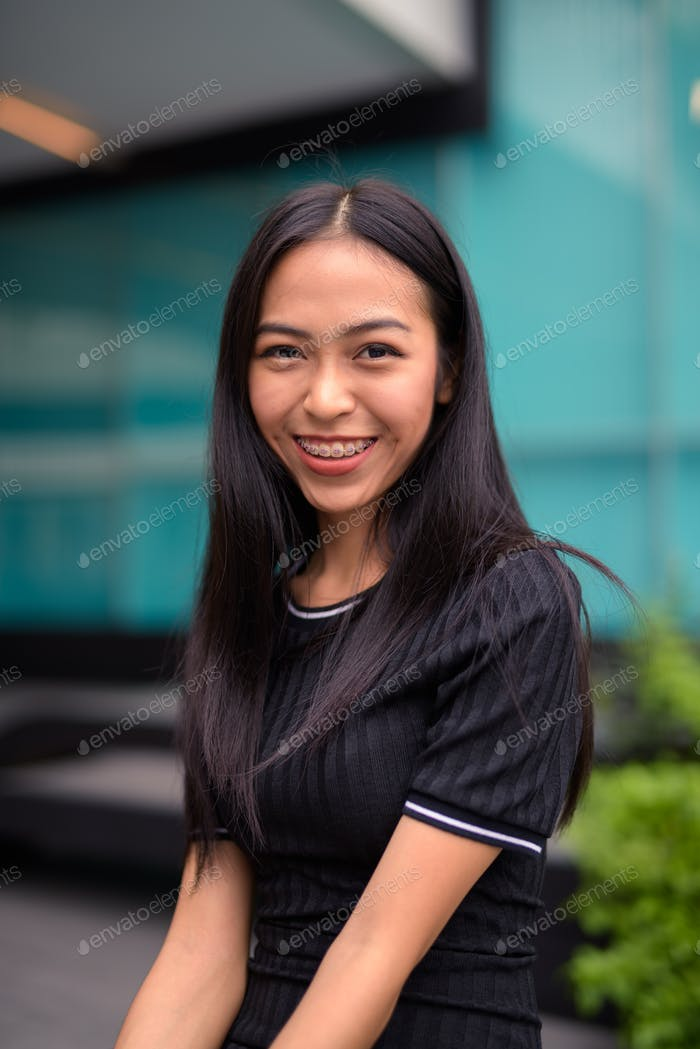 Happy young beautiful Asian tourist woman at the mall outdoors