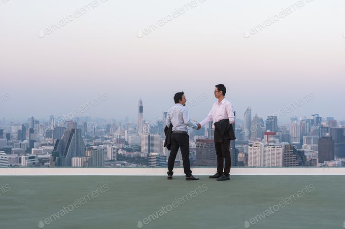 Couple businessman shake hand for deal the business over the cityscape background