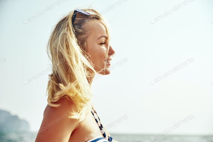 Smiling young woman enjoying the ocean view from a boat