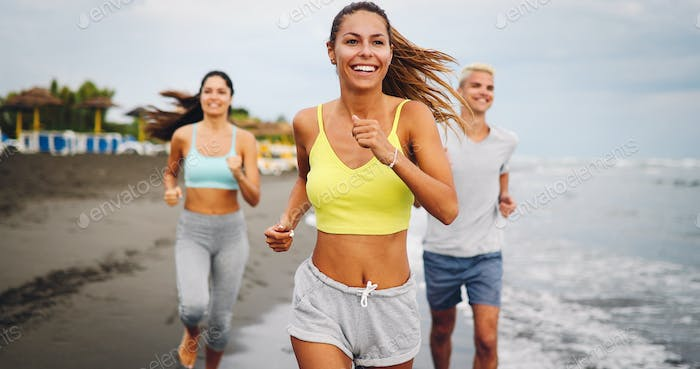 Fitness, sport, friendship and healthy lifestyle concept . Group of happy people jogging