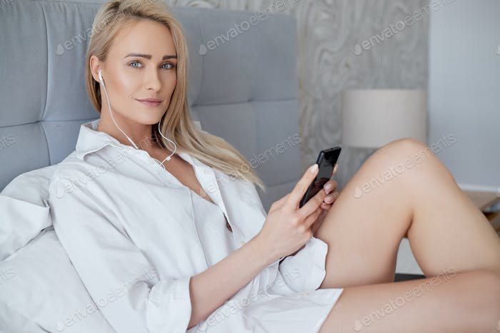 Beautiful, smiling blond woman lying in white bed and using a smartphone