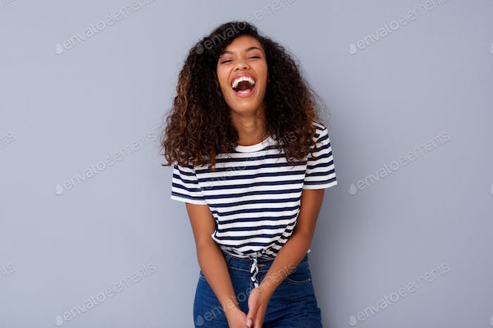 young black woman laughing against gray wall
