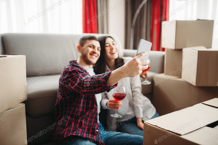 Couple makes selfie against boxes, moving to house