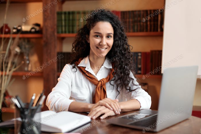 Confident woman posing sitting at desk with laptop