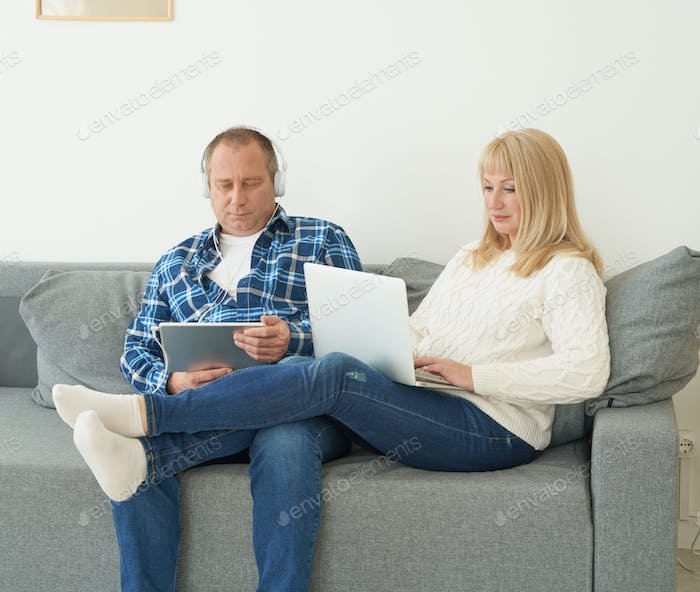 Full length portrait of mature couple with digital addiction at home