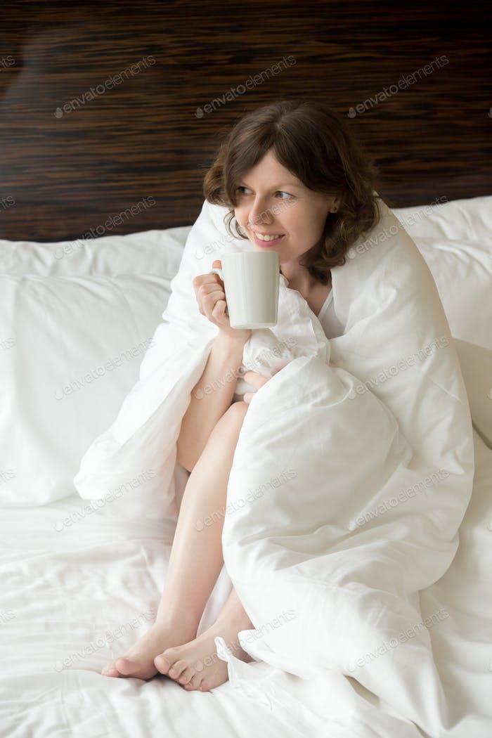 Young woman under warm blanket