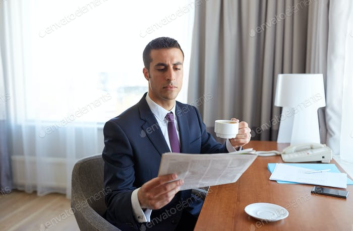 businessman reading newspaper and drinking coffee