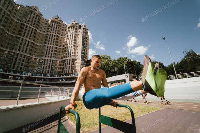 Strong man doing exercises on uneven bars in outdoor street gym
