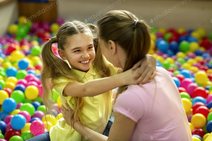Cheerful girl hugging her mother in ball pit at indoor kids playground