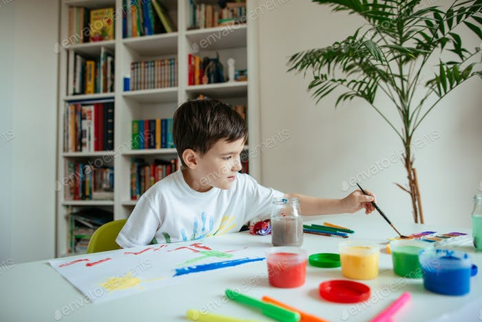 Schoolboy reaching for watercolor with paintbrush in his hand.